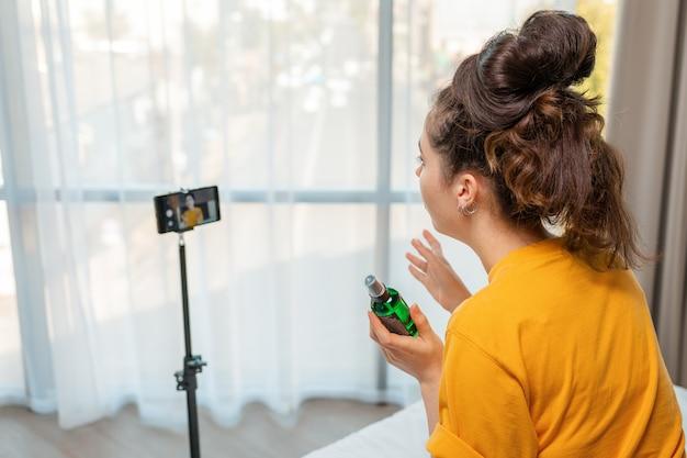 Redes sociales. una joven vloguera transmitiendo video en vivo en un teléfono inteligente y hablando sobre un nuevo cosmético. vista trasera.