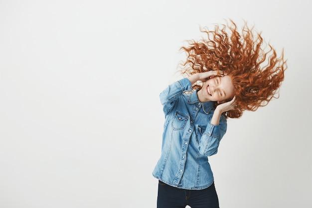 Redhead hermosa niña sonriente sonriendo sacudiendo el cabello rizado ojos cerrados.