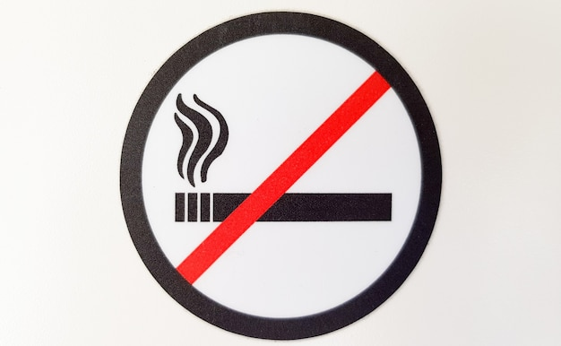 Redondo rojo y negro señal de no fumar, pegatina en un lugar público sobre un fondo blanco.