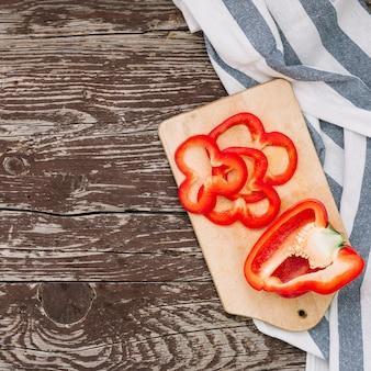 Reducido a la mitad y una rodaja de pimiento rojo en una tabla de cortar sobre la mesa de madera