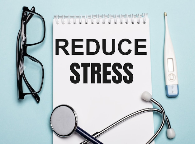 Reducir el estrés escrito en un bloc de notas blanco junto a un estetoscopio, gafas y un termómetro electrónico sobre un fondo azul claro. concepto médico.