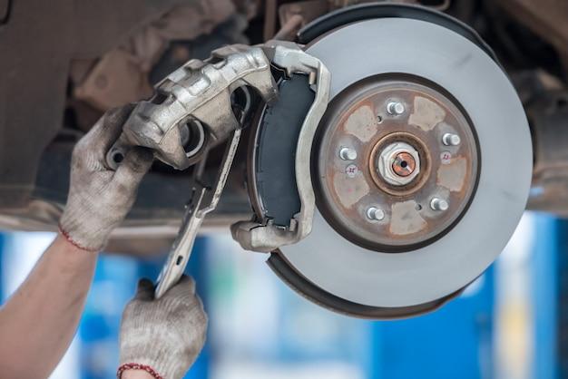 Reemplazar las pastillas de freno en el centro de servicio el mecánico de automóviles con guantes blancos está a punto de cambiar las pastillas de freno del automóvil