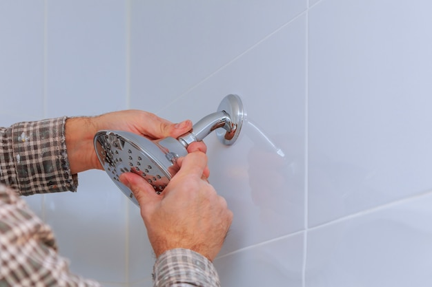 Reemplazo de la plomería en el soporte de ducha de mano montado en el baño con un cabezal de ducha ajustable en altura.
