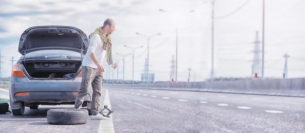 Reemplazo de la rueda de un automóvil en la carretera. un hombre que trabaja con neumáticos al margen.