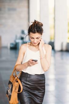Refinada mujer sonriente caminando y escribiendo o leyendo mensajes sms