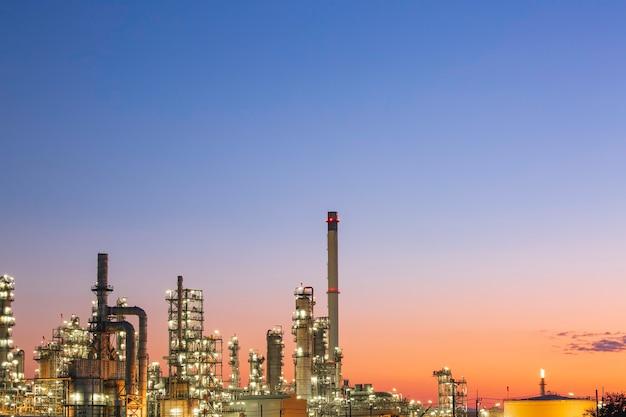 Refinería de petróleo y planta y columna de torre de la industria petroquímica en petróleo y gas industrial con cielo azul de nubes el fondo de la salida del sol