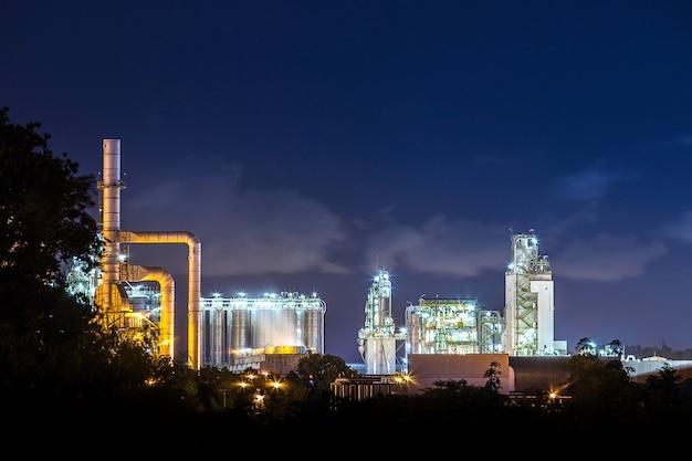 Refinería de petróleo y planta petroquímica con torre de enfriamiento.