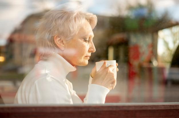 Reflejando mujer senior bebiendo café