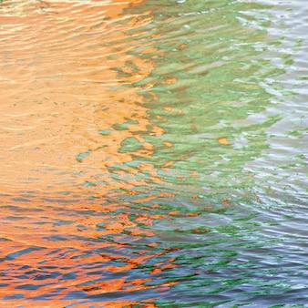 Reflejo de las hermosas y coloridas luces sobre las ondas en el agua