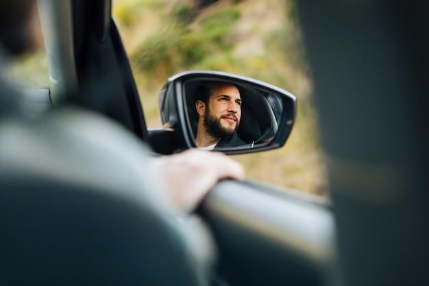 Reflejo de macho feliz en espejo lateral de auto
