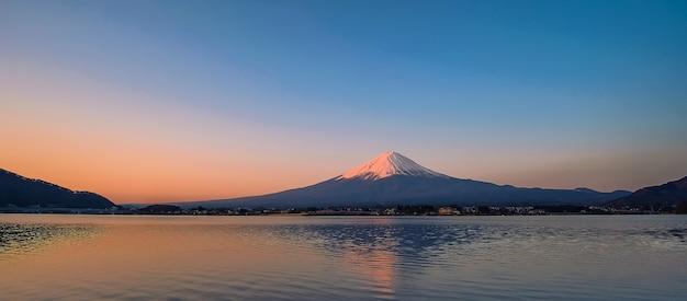 Reflejo de la montaña fuji con nieve coronada por la mañana amanecer