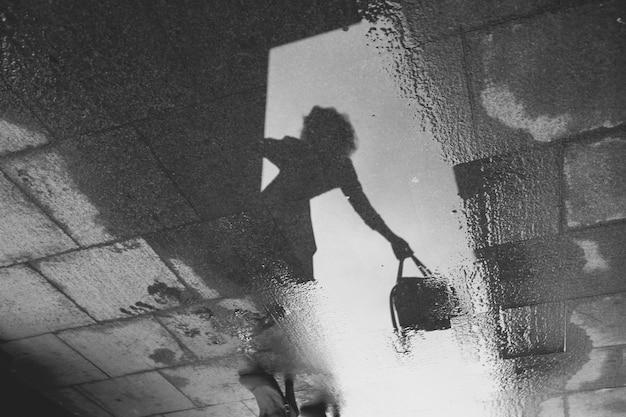 Reflejo de una niña con una bolsa en la mano en un charco sobre un pavimento de piedra. en blanco y negro