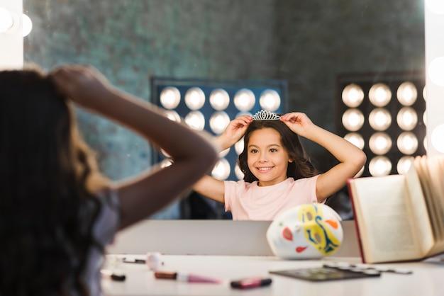 Reflejo de niña sonriente con corona en el backstage