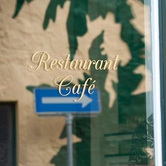 Reflejo de signo de calle de flecha en la ventana del restaurante