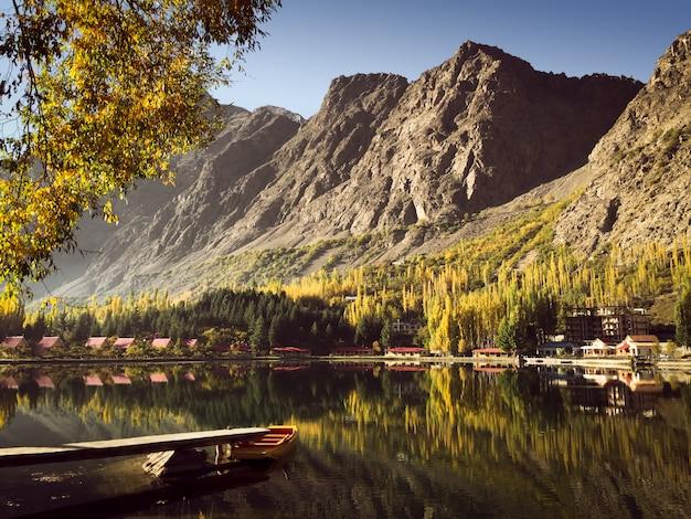 Reflexión en el agua de la montaña y árboles coloridos en otoño con un barco atracado en el lago.
