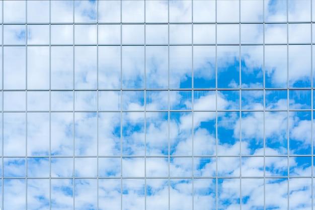 Reflexión del cielo y las nubes en la pared de cristal.