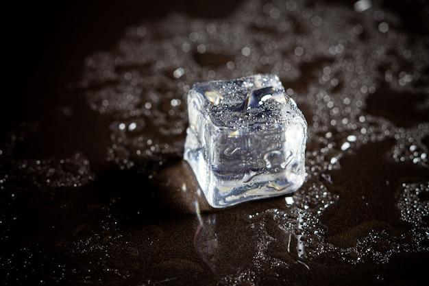 Reflexión de los cubitos de hielo en el fondo negro de la tabla.