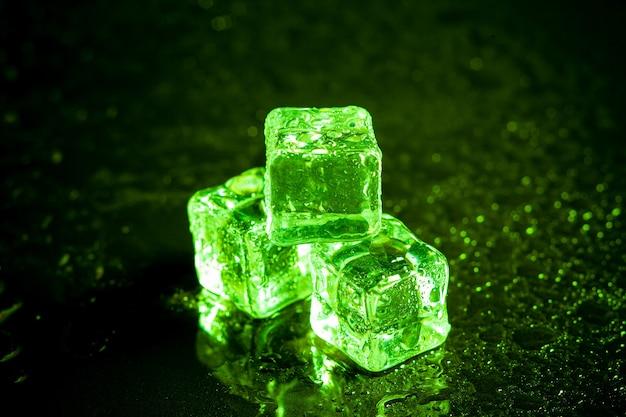 Reflexión de cubitos de hielo verde sobre fondo negro de la tabla.