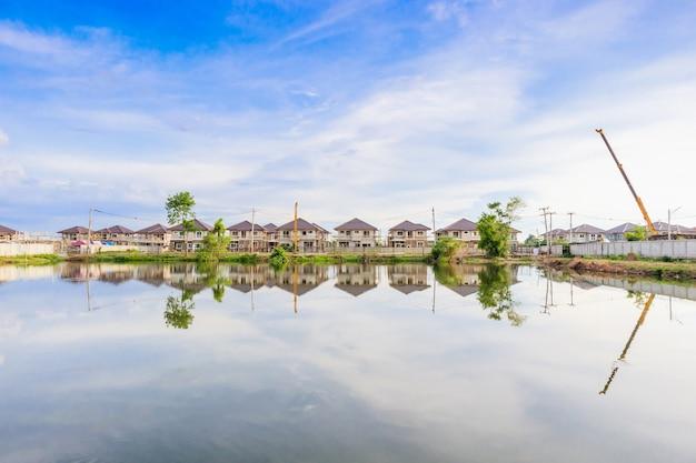Reflexión del edificio de la nueva casa con agua en el lago en el sitio de construcción de la urbanización residencial con nubes y cielo azul