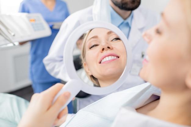 Reflexión en el espejo de la sonrisa sana de la paciente mujer sonriente bastante joven de clínicas dentales después del procedimiento de blanqueamiento dental por su dentista