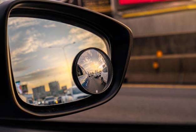 Reflexión del flujo de tráfico en la carretera asfaltada en el espejo lateral del suv azul. espejo retrovisor para automóvil con espejo convexo para una conducción segura.