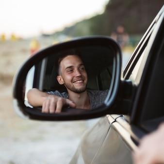 Reflexión del hombre en el espejo del coche