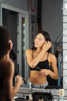 Reflexión de joven bella mujer aplicando su maquillaje
