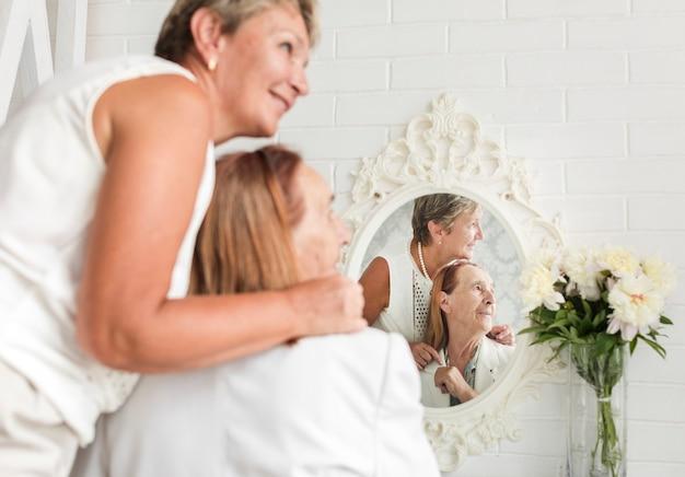 Reflexión de madre e hija en el espejo mirando a otro lado