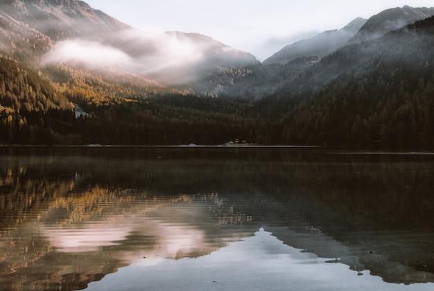 Reflexión de montaña sobre cuerpo de agua bajo un cielo blanco en