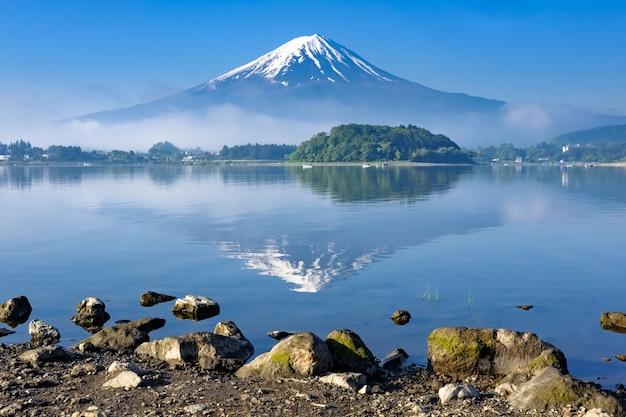 Reflexión del monte. fuji con primer plano de la orilla de roca, lago kawaguchiko, yamanashi