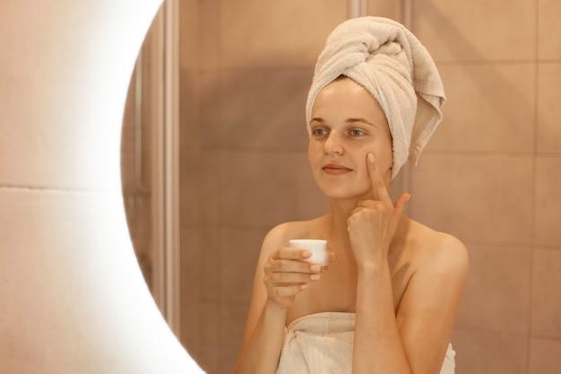 Reflexión de una mujer adulta joven en el espejo aplicando crema cosmética en la cara, poniéndose argent nutritivo en su piel facial en el baño, posando con una toalla en la cabeza.