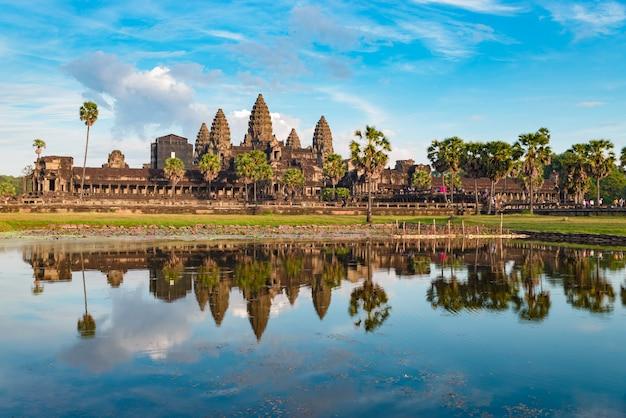 Reflexión principal de la fachada del cielo azul del día soleado de angkor wat en luz de la puesta del sol del estanque de agua