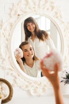 Reflexión de sonriente madre e hija con caja de regalo de explotación