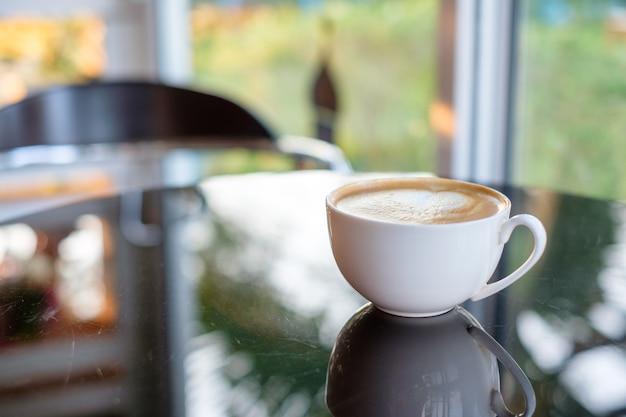 Reflexión de la taza de café sobre la mesa de cristal en el café