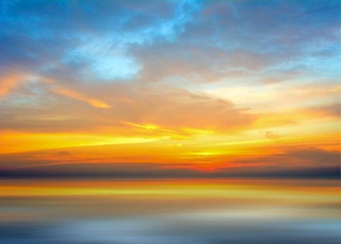Reflexión viva hermosa del cielo de la puesta del sol y del amanecer en el agua