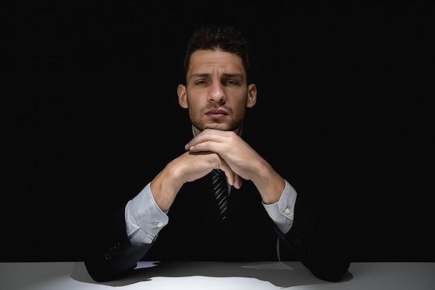 Reflexionando sobre un traje negro con las manos en la barbilla en sombra oscura