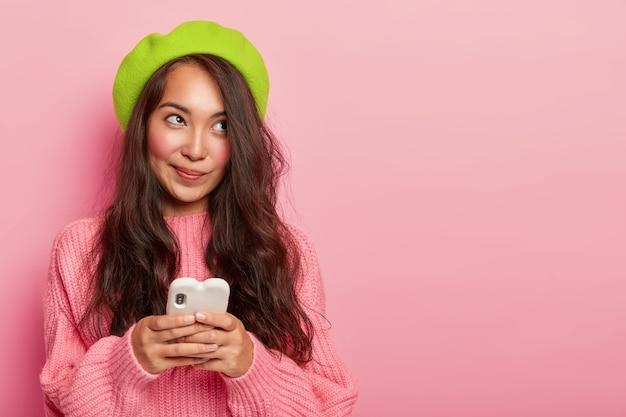 Reflexiva adolescente coreana con cabello largo y oscuro, usa el teléfono móvil para enviar mensajes en línea, usa boina verde y suéter de punto