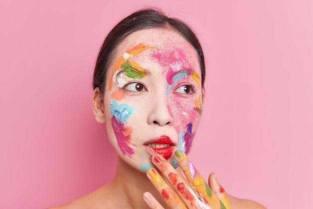 Reflexiva hermosa mujer asiática manchada con pinturas de acuarelas brillantes trabaja como artista se encuentra sin camisa aislado sobre fondo rosa