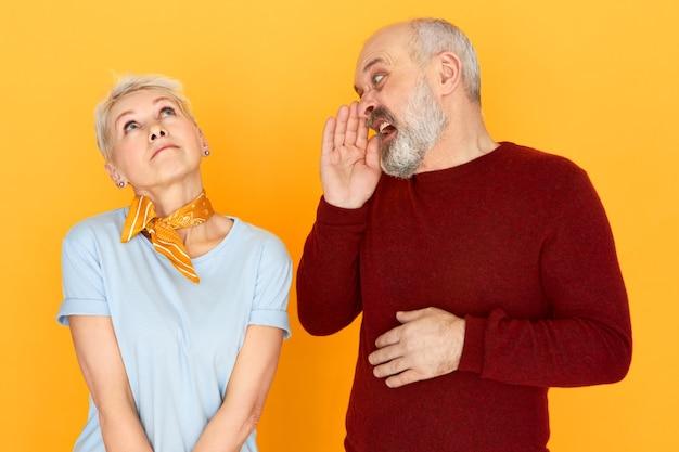 Reflexiva hermosa mujer de mediana edad despreocupada mirando hacia arriba en las nubes soñando, sin escuchar los gritos de su esposo anciano disgustado con barba sosteniendo la mano en la boca y gritando
