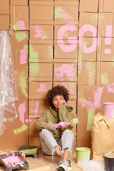 Reflexiva joven afroamericana sentada en el piso se toma un descanso después de renovar la nueva casa sostiene un cepillo para pintar paredes piensa en nuevos movimientos interiores en el nuevo piso tiene descanso después de la renovación de la casa