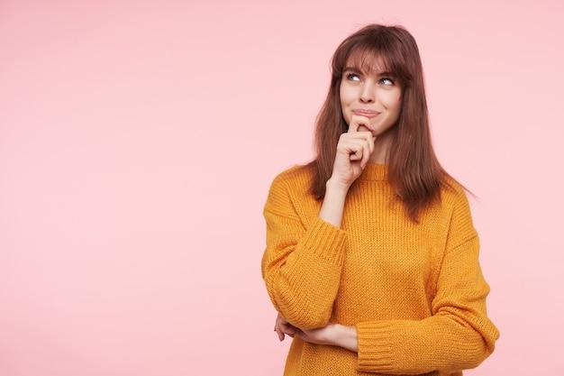Reflexiva joven encantadora dama de cabello oscuro con maquillaje natural sosteniendo su barbilla con la mano levantada y mirando soñadoramente hacia arriba mientras está de pie sobre la pared rosa