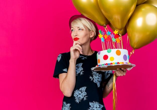 Reflexiva joven rubia fiestera con sombrero de fiesta sosteniendo globos y pastel de cumpleaños con estrellas tocando la barbilla mirando al lado aislado sobre fondo carmesí con espacio de copia