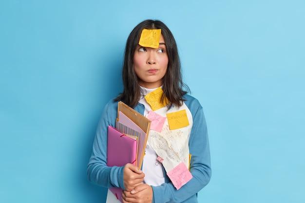 Reflexiva mujer asain tiene notas adhesivas en la ropa y la frente, pensativa, trabaja duro durante la fecha límite, sostiene carpetas con documentos.