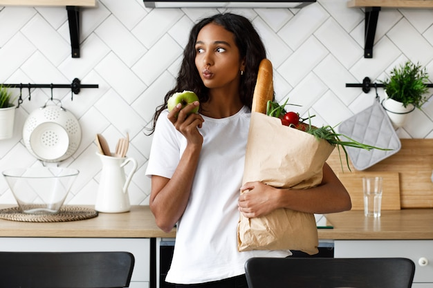Reflexiva mujer mulata sostiene el paquete lleno de verduras frescas en una mano y manzana mordida en la otra, en la moderna cocina blanca