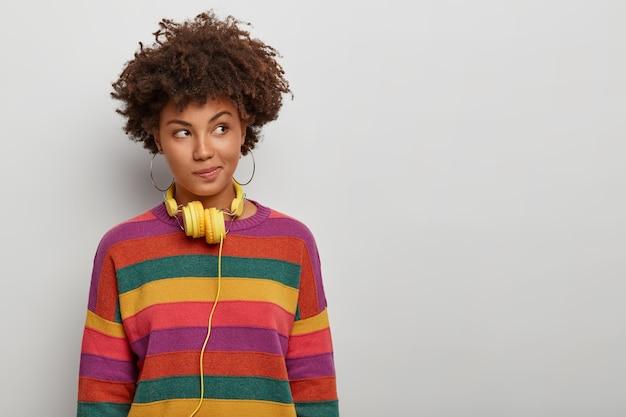 Reflexiva mujer de pelo rizado mira a un lado con expresión pensativa, usa auriculares y un jersey a rayas, tiene un plan en mente, posa sobre fondo blanco