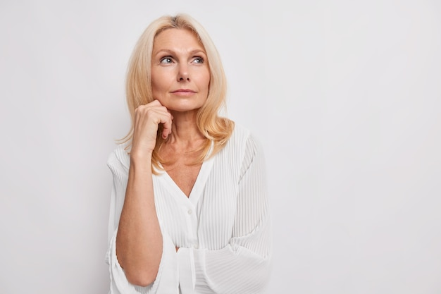 Reflexiva mujer rubia de mediana edad reflexiona sobre algo que mantiene la mano cerca de la cara tiene una piel sana maquillaje mínimo hace que la elección use blusa blanca plantea espacio de copia en blanco interior para su promoción