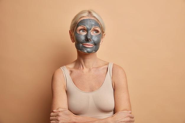 Reflexiva mujer rubia senior aplica belleza coral negra máscara antienvejecimiento en la cara mantiene los brazos cruzados vestidos con top casual aislado en la pared beige