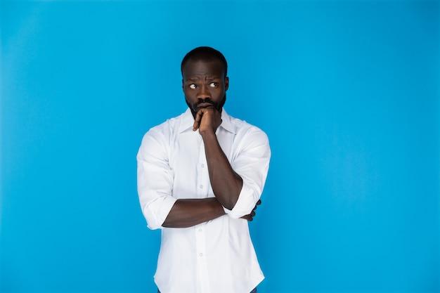 Reflexivo afroamericano en camisa blanca