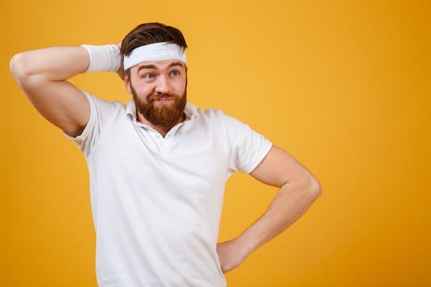 Reflexivo deportista barbudo rascándose la cabeza