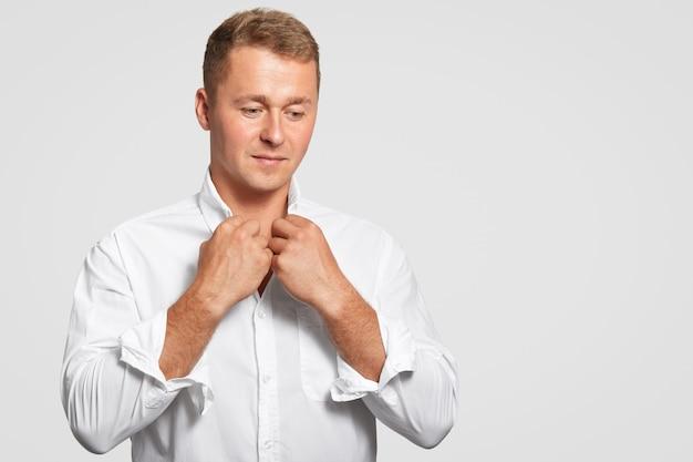 Reflexivo hombre de negocios decidido en elegante camisa blanca formal, piensa en algo, enfocado hacia abajo, tiene una apariencia atractiva, se para contra la pared blanca con espacio en blanco para copiar su texto